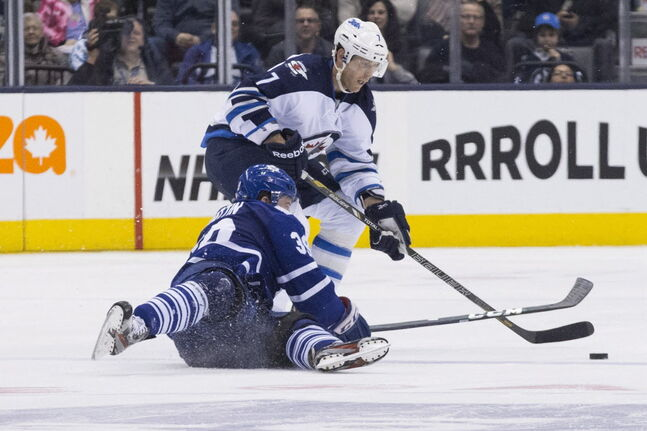 Winnipeg Jets' Derek Meech (right) battles for the puck with Toronto Maple Leafs' Matt Frattin.