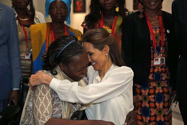 US actress Angelina Jolie, right, Special Envoy of the United Nations High Commissioner for Refugees, hugs Neema Namadamu of the Democratic Republic of Congo at the 'End Sexual Violence in Conflict' summit in London, Wednesday, June 11, 2014. Namadamu formed an organisation that uses digital media to empower women demanding peace in eastern Congo. She formed it earlier this year after her own 25-year -old daughter was attacked. The Summit welcomes governments from over 100 countries, over 900 experts, NGOs, Faith leaders, and representatives from international organisations across the world. (AP Photo/Lefteris Pitarakis, pool)