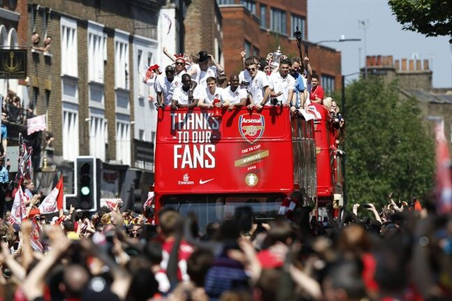 Arsenal's soccer team players parade through the street of London Sunday, May 18, 2014, on a open top bus in celebration of their English FA Cup win. Aaron Ramsey scored in extra time to clinch a 3-2 victory over Hull on Saturday, making Arsenal FA Cup Winners for the fifth time in Arsene Wenger's 14-year tenure as coach of The Gunners. (AP Photo/Sang Tan)