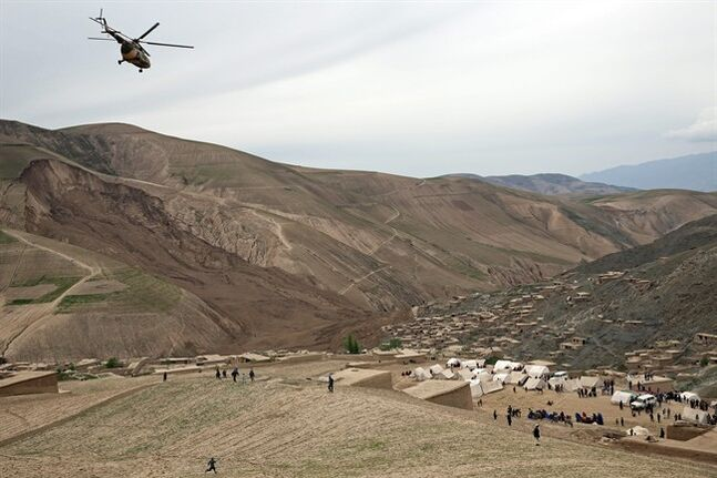 Survivors walk near the site of Friday's landslide that buried Abi-Barik village in Badakhshan province, northeastern Afghanistan, Sunday. As Afghans observed a day of mourning Sunday for the hundreds of people killed in a horrific landslide, authorities tried to help hundreds of families displaced by the torrent of mud that swept through their village.