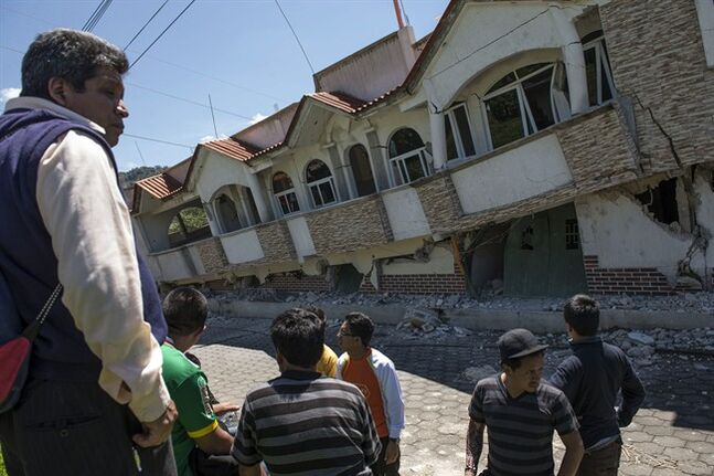 Neighbors gather outside homes that collapsed during an earthquake in San Pedro, Guatemala, Monday, July 7, 2014. A magnitude-6.9 earthquake on the Pacific Coast jolted a wide area of southern Mexico and Central America Monday. (AP Photo/Oliver de Ros)