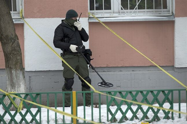 A police officer uses a metal detector outside a Moscow school on Monday, Feb. 3, 2014. An armed teenager burst into his Moscow school on Monday and killed a teacher and policeman before being taken into custody, investigators said. None of the children who were in School No. 263 were hurt, said Karina Sabitova, a police spokeswoman at the scene. The student also wounded a second police officer who had responded to an alarm from the school, she said. (AP Photo/Alexander Zemlianichenko)