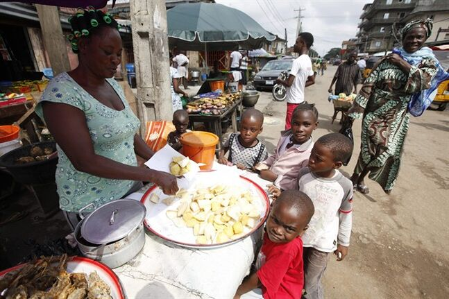 Children buy fried potatoes on a street in Lagos, Nigeria, Thursday Aug. 7, 2014. West Africans battling to contain the spread of Ebola will have to wait for months until a potentially life-saving experimental drug used on two Americans infected with the dreaded disease could even be made, officials said. There's little of the experimental drug ZMapp available now, and even if it can be made in large quantities, its safety and effectiveness haven't been tested yet. (AP Photo/Sunday Alamba)
