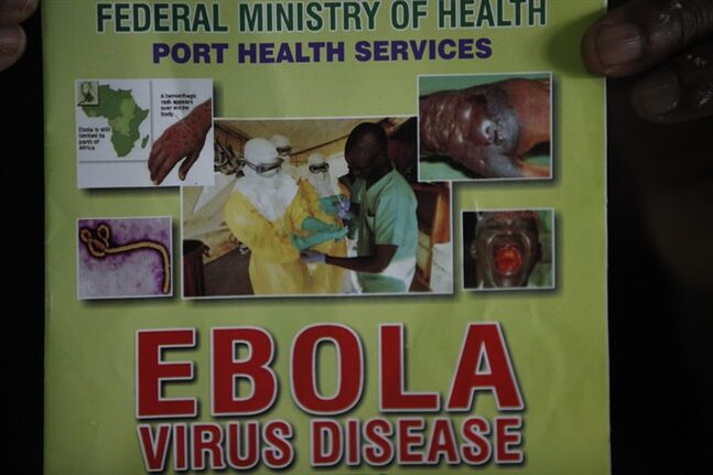 Nigeria health official display a leaflet explaining Ebola Virus Disease at the arrival hall of Murtala Muhammed International Airport in Lagos, Nigeria, Monday, Aug. 4, 2014. Nigerian authorities on Monday confirmed a second case of Ebola in Africa's most populous country, an alarming setback as officials across the region battle to stop the spread of a disease that has killed more than 700 people. (AP Photo/Sunday Alamba)