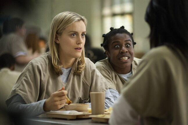 FILE - This image released by Netflix shows Taylor Schilling, left, and Uzo Aduba in a scene from