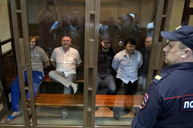 From left: Ibragim Makhmudov, Lom-Ali Gaitukayev, Dzhabrail Makhmudov, Rustam Makhmudov and Sergey Hadjikurbanov accused of the murder of journalist Anna Politkovskaya, await the judge's verdict in a glass cage, at the Moscow City Court, in Moscow, Russia, Monday.
