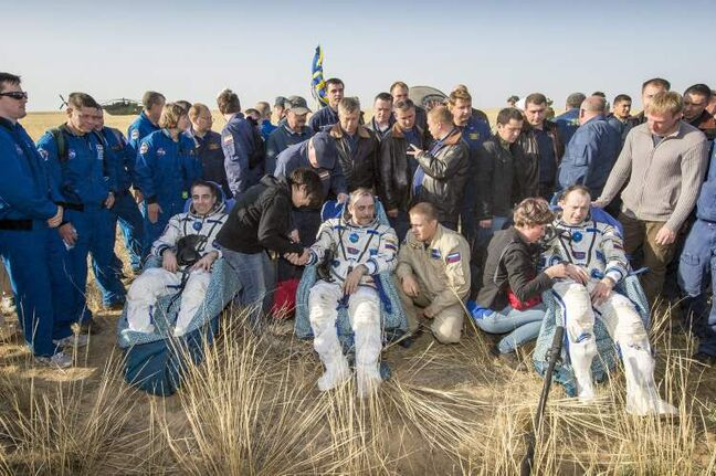 Expedition 36 flight engineer Chris Cassidy of NASA, left, commander Pavel Vinogradov of the Russian Federal Space Agency (Roscosmos), centre, and flight engineer Alexander Misurkin of Roscosmos, sit in chairs outside the Soyuz capsule just minutes after they landed in a remote area near the town of Zhezkazgan, Kazakhstan, on Wednesday. Vinogradov, Misurkin and Cassidy returned to Earth after 166 days on the International Space Station.