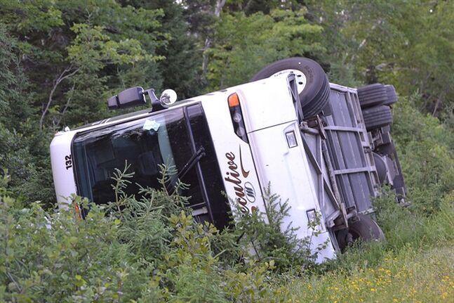 A tour bus is overturned on the Cabot Trail highway in Nova Scotia on Sunday, July 13, 2014. A woman has died in hospital after a tour bus in Nova Scotia crashed on the Cabot Trail highway and ended up on its side, the RCMP said Monday. THE CANADIAN PRESS/Cape Breton Post-TJ Colello