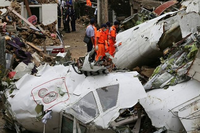 Rescue workers survey the wreckage of TransAsia Airways Flight GE222 on the Taiwanese island of Penghu Thursday, July 24, 2014. The plane attempting to land in stormy weather crashed on the island late Wednesday, killing more than 40 people and wrecking houses and cars on the ground. (AP Photo) TAIWAN OUT