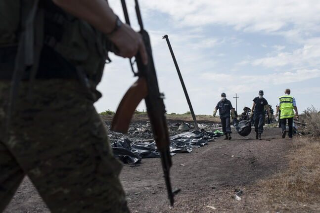 Ukrainian emergency workers carried a victim's body in a body bag last week as a pro-Russian fighter guarded the crash site of Malaysia Airlines Flight 17 near the village of Hrabove in eastern Ukraine.