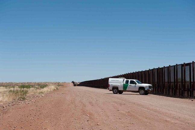 A U.S. Border Patrol truck drives the border road on the southernmost limit of a Naco, Ariz. ranch, April 28, 2014.