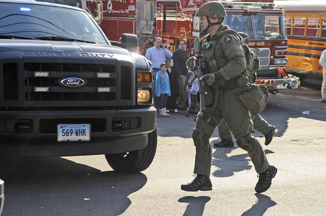 A state police SWAT team member runs to a police car as Sandy Hook Elementary School in Newtown, Connecticut is evacuated after a shooting, Friday, December 14, 2012.