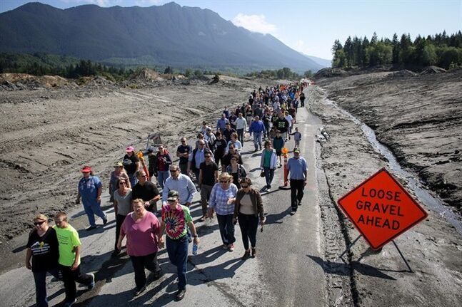 Hundreds of Oso, Darrington and Arlington, Wash. residents walk on State Route 530 near Oso, Wash. on Saturday, May 31, 2014 to pay tribute to those killed before the highway was reopened to cars. A little more than two months after the Oso mudslide destroyed a neighborhood and killed 43 people, the highway through the heart of the slide reopened to vehicle traffic. (AP Photo/seattlepi.com, Joshua Trujillo)