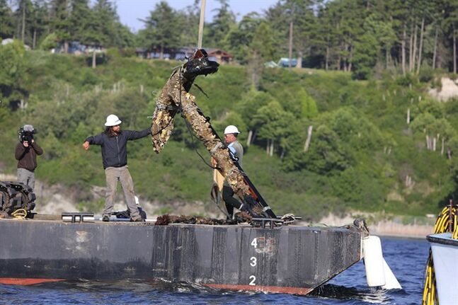 Work crews pull out an anchor from Admiralty Inlet off Whidbey Island, Wash., on Monday, June 9, 2014. The anchor was found six years ago by sea-cucumber diver Doug Monk who formed Anchor Ventures with amateur historian Scott Grimm to bring it to the surface. The anchor may be the anchor lost by the HMS Chatham as it explored with Capt. George Vancouver's HMS Discovery in 1792. The 900-pound anchor was taken Monday to the Northwest Maritime Center in Port Townsend. (AP Photo/The Seattle Times, Steve Ringman) SEATTLE OUT; USA TODAY OUT; MAGS OUT; TELEVISION OUT; NO SALES; MANDATORY CREDIT TO BOTH THE SEATTLE TIMES AND THE PHOTOGRAPHER