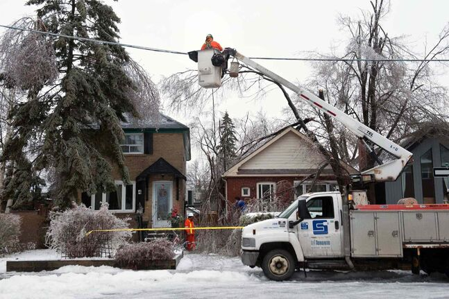 Workers from Stacey Electric, a Toronto Hydro subcontractor, work to repair downed power lines around Victoria Park and Denton Avenues in Scarborough, Monday, after a severe ice storm hit Toronto.