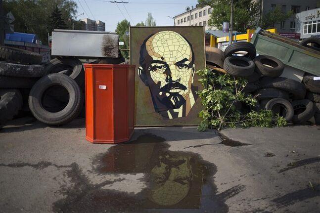 A portrait of Bolshevik leader Vladimir Lenin is set into a barricade in the center of Slovyansk, eastern Ukraine, Saturday, May 3, 2014. The city has become the focus of an armed pro-Russian, antigovernment insurgency that aspires to give the eastern regions of Ukraine full autonomy. (AP Photo/Alexander Zemlianichenko)