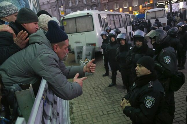 Pro-European Union activists, left, talk to police officers guarding supporters of Yanukovych's party of Regions during their rally at Independence Square in Kiev, Ukraine, Saturday, Dec. 14, 2013. The opposition has called for a vast turnout Sunday. Rallies on the previous two Sundays drew hundreds of thousands of protesters. That same day, Yanukovych's Party of Regions has called for a pro-government demonstration that it claims will bring 200,000 people to Kiev. (AP Photo/Sergei Grits)
