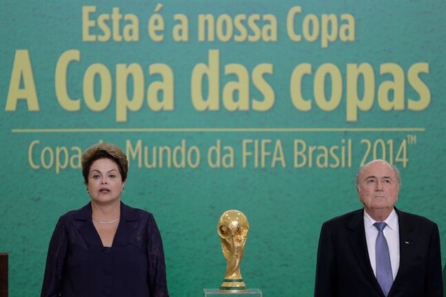 FILE - In this June 2, 2014, file photo, Brazil's President Dilma Rousseff and FIFA President Joseph Blatter stand during the playing of the Brazilian national anthem during a ceremony where Blatter presented the 2014 World Cup trophy to Rousseff, at Planalto presidential palace, in Brasilia, Brazil. For Rousseff, who has seen her approval rating steadily fall as she gears up for a re-election run, hosting the World Cup has become a potential political liability reminding voters of her failure to deliver on promises and live up to a reputation for being a hard-driving manager. (AP Photo/Eraldo Peres,File)