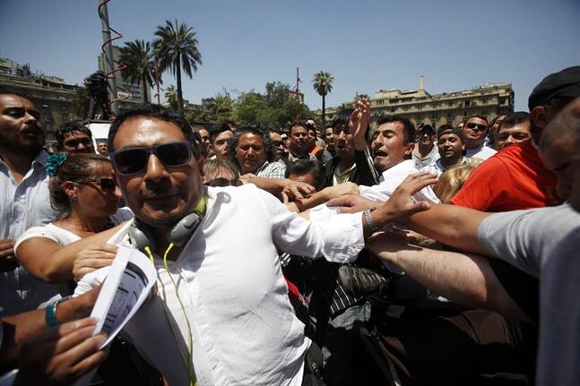 A Peruvian citizen, left, is attacked by a group of Chilean nationalists after defending the Peruvian legal position after the ruling by the International Court of Justice, in Santiago, Chile, Jan. 27, 2014. The United Nations' highest court set a maritime boundary between Chile and Peru on Monday, granting the latter a bigger piece of the Pacific Ocean but keeping rich coastal fishing grounds in Chilean hands. (AP Photo / Luis Hidalgo).
