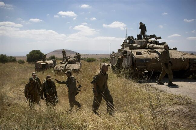 Israeli soldiers work on their tanks following the first death on the Israeli side of the Golan since the Syrian civil war erupted more than three years ago, near the Israeli village of Alonei Habashan, in the area of Tel Hazeka, close to the Quneitra border crossing in the Israeli-controlled Golan Heights, Sunday, June 22, 2014. A civilian vehicle in the Israeli-controlled Golan Heights was targeted by forces in neighboring Syria on Sunday in an attack that killed a 15-year-old boy and prompted Israeli tanks to retaliate by firing on Syrian government targets, the Israeli military said. (AP Photo/Oded Balilty)