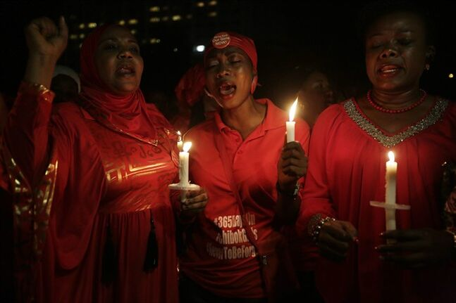 People hold candles as they sing during a vigil to mark the one year anniversary of the abduction of girls studying at the Chibok government secondary school, Abuja, Nigeria, Tuesday, April 14, 2015. On the first anniversary of the day 276 schoolgirls were snatched in the middle of the night as they prepared to write science exams at their boarding school in northeastern Nigeria, President-elect Muhammadu Buhari said he cannot promise to find the 219 who are still missing. (AP Photo/Sunday Alamba)