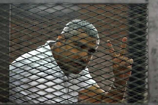 Canadian-Egyptian journalist Mohammed Fahmy gestures from the defendant's cage during a sentencing hearing in a courtroom in Cairo, Egypt, Monday, June 23, 2014.(AP Photo/Ahmed Abd El Latif, El Shorouk Newspaper) EGYPT OUT