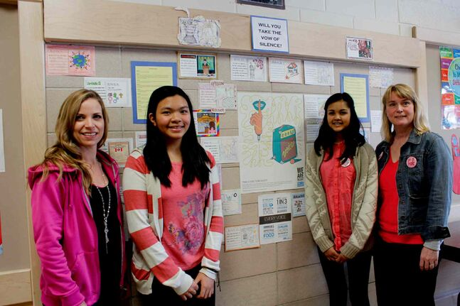 From left to right: Sargent Park School teacher Michele Lanyon and students Heather Jimenez, Seemeen Mohamed, and teacher Maureen Wilson stand next to a wall decorated with article cards depicting children's rights.