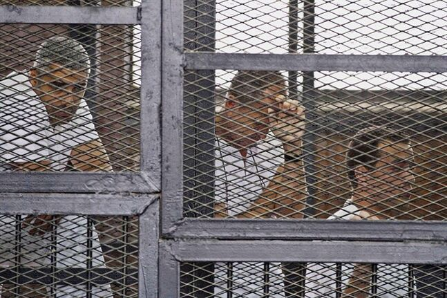 Mohammed Fahmy, (left to right) Canadian-Egyptian acting bureau chief of Al-Jazeera, Australian correspondent Peter Greste, and Egyptian producer Baher Mohamed appear in a defendant's cage along with several other defendants during their trial on terror charges at a courtroom in Cairo in this Thursday, May 15, 2014 file photo, from left, . After a trial which has drawn the attention of media organizations and human rights advocates around the world, the 40-year-old Egyptian-Canadian journalist and his two colleagues are now expected to learn on Monday whether they'll be found guilty or set free. THE CANADIAN PRESS/AP/Hamada Elrasam