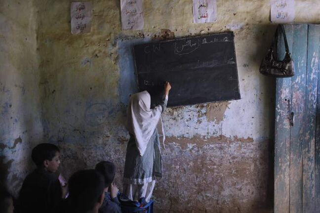 A Pakistani student, stands on a chair to reach the blackboard and write on it, during a class at the EHD foundation school, in Islamabad, Pakistan. A teenage activist recently shot and critically wounded by the Taliban risked her life to attend school, but the threat from the militant group is just one of many obstacles Pakistani girls face in getting an education. Others include rampant poverty, harassment and the government's failure to prioritize education spending. (AP Photo/Nathalie Bardou)