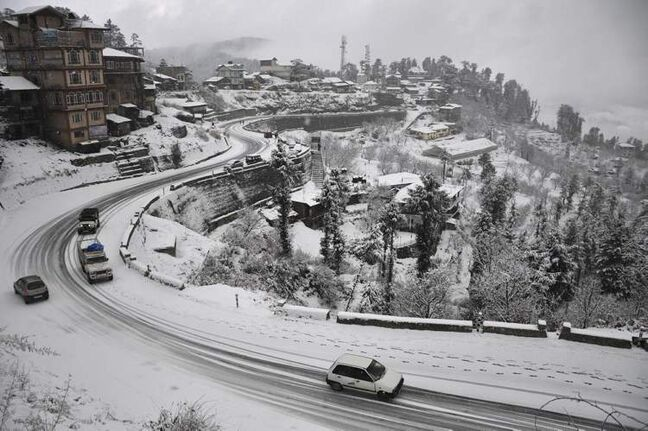 Vehicles move on a snow-covered road after the season's first snowfall near the northern hill town of Shimla, India, Tuesday, Dec. 11, 2012. The snowfall is expected to trigger a rush of tourists to the area. (AP Photo/Mainka Gill)