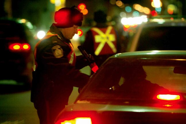 In this file photo, a police officer talks to a driver at a checkstop. The Winnipeg Police Service Central Traffic Unit recently released results from last year's annual Festive Checkstop program, when more than 4,000 motorists were stopped.