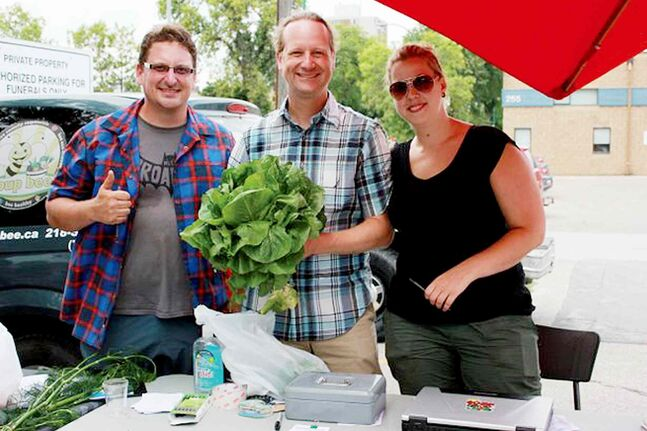 Rob Altemeyer, MLA for Wolseley, shows off one of the largest heads of lettuce he's ever seen at the West Broadway Farmers' Market, along with Good Food Club co-ordinators Damien Gagne and Ailene Deller.