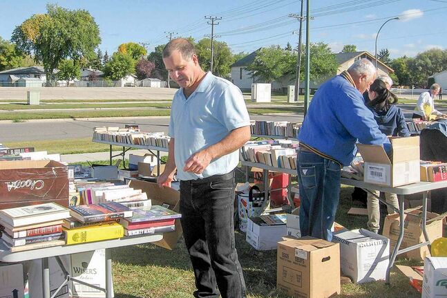 Jim Rondeau, MLA for Assiniboia, and volunteers help set up for last year's Assiniboia's Literacy Book Exchange. This year's exchange is set for Sat., Sept. 27.