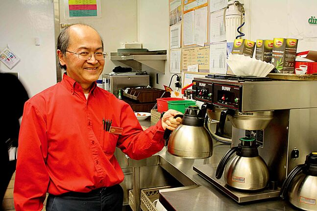 Raymond Tan, manager of Denny's in the Flying J Travel Plaza in Headingley, shows off a couple of the 600 pots of coffee his restaurant brews each week.