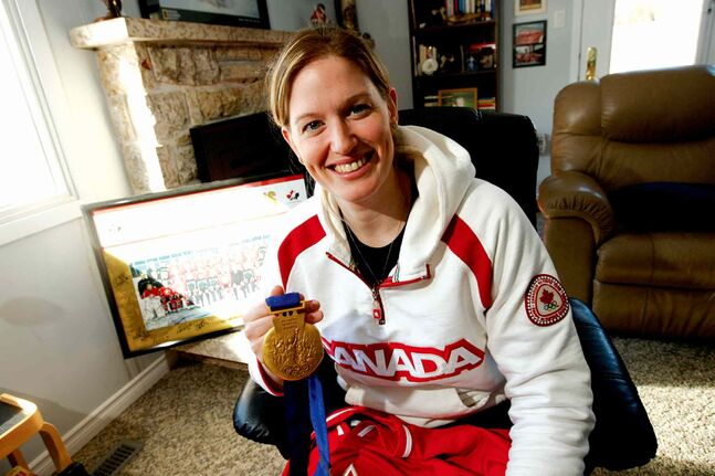 In this 2010 file photo, Sami Jo Small is pictured with her Olympic gold medal and memorabilia from her hockey career.