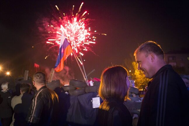 People watch fireworks celebrating the declaration of independence for Donetsk region at barricades in front of a regional administration building that was recently seized by pro-Russian activists in Donetsk, Ukraine, Monday, May 12, 2014, with a Russian national flag is in the background. Pro-Moscow insurgents in eastern Ukraine declared independence Monday, putting pressure on Kiev to hold talks with the separatists. (AP Photo/Alexander Zemlianichenko)