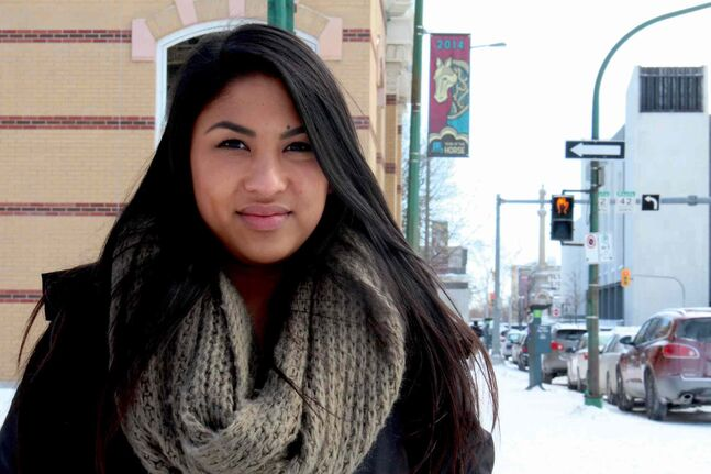 Victoria Buen, a graphic design student at Red River College, designed the Year of the Horse banners (behind her). There are now 18 banners with her design all over Winnipeg's Chinatown.