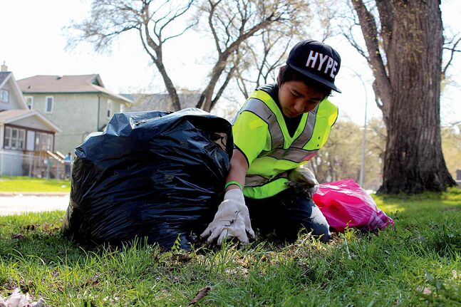 Delaney Flett, 14, scoops up some dead leaves in front of a house on Pritchard Avenue during the William Whyte Residents Association annual community cleanup on Fri., May 23.