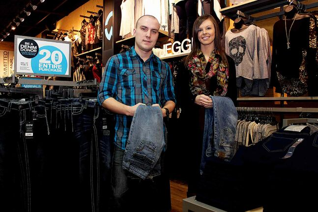 Wayne Vernon, marketing manager with Warehouse One, and Damara Ewan, assistant manager at the retailer's Kildonan Place location, hold pairs of jeans which were donated to the store. Warehouse One's Denim Donor campaign, which runs until Feb. 9, allows customers to receive 20% off their entire purchase with the donation of a gently used pair of jeans. Warehouse One donates jeans to shelters across Canada.