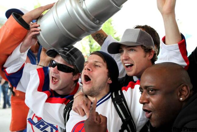 Hundreds of NHL Hockey fans scream under the canopy at The Forks to celebrate their return. Steve Kaltchev (centre with black toque) celebrates with his friends and a plastic Stanley Cup at the Forks Tuesday afternoon.
