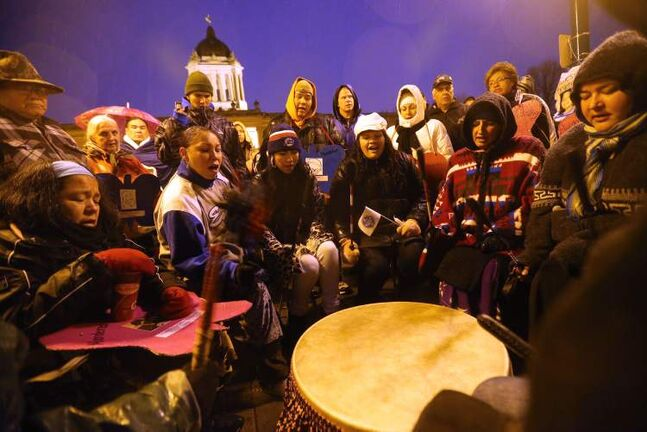 People huddle in the rain as drummers play at last year's vigil for missing and murdered women at the legislative building on Oct. 4, 2012.