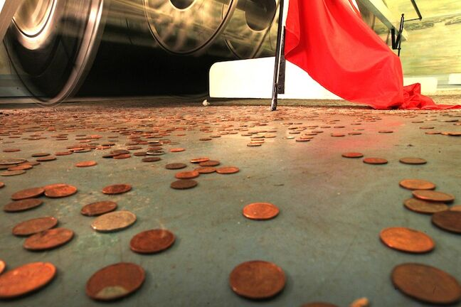 Coins sit on the floor of a waterless tank next to a spinning paddlewheel. Water hasn't been in its tank for some time but patrons still use it as a wishing well.