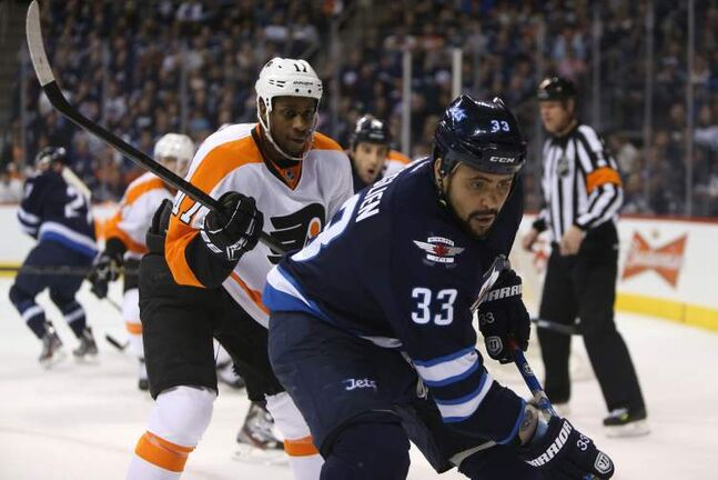 Winnipeg Jets' Dustin Byfuglien (33) is chased into the corner by Philadelphia Flyers' Wayne Simmonds (17) during the second period NHL hockey action, Saturday. The Jets returned from a poor first period and defeated the Flyers 4-1.