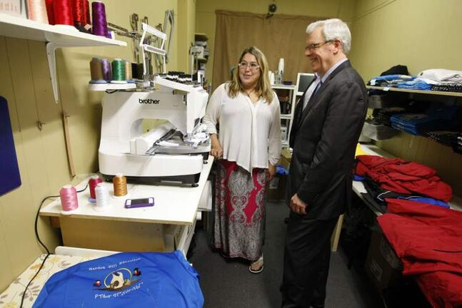 Michelle Cameron of Dreamcatcher Promotions shows Premier Greg Selinger the firm's new computerized sewing machine.