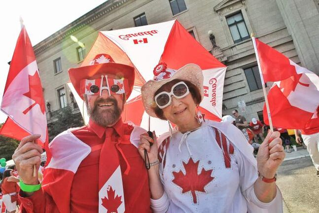 Eliza (Right) and Allan Kingdon from Erickson, MB show off their red and white at the Living Flag event on the grounds of the Manitoba legislature Monday morning.