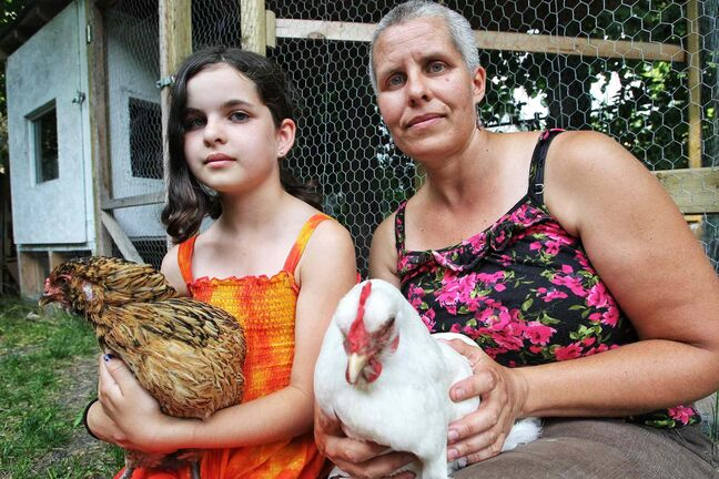 Stacie Gottfried with her daughter Shanti and two hens they have in a backyard coop.  She will have to get rid of the animals under a city bylaw.