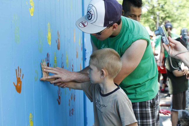 Neighbourhood children put their hand prints on a freshly painted building at Machray Park in 2013.