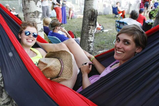 Megan Barrymore (right) and wife Mandolyn share a hammock in a shady nook of the festival grounds.
