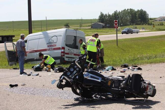 Paramedics give medical attention to a woman involved in a collision between a motorcycle and a cube van at the intersection of Highway 1 and Highway 270 just west of Brandon on Friday afternoon.