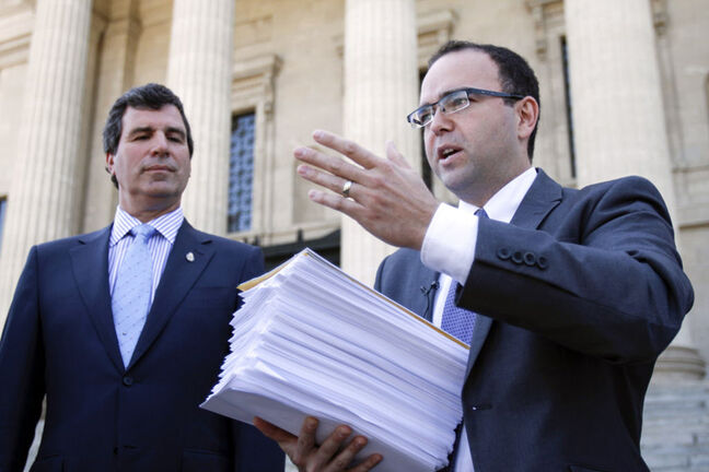 Colin Craig (right) from the Canadian Taxpayers Federation and PC MLA Reg Helwer with over 8000 signatures collected from Manitobans against the PST increase on the steps of the Manitoba Legislature.